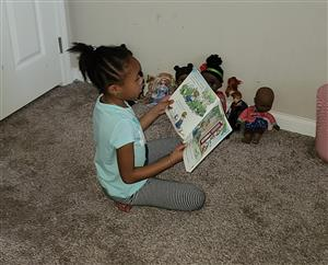 Student reads to her dolls