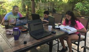 Family of three in online learning outdoors on a beautiful patio