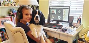 Girl learning in teams with dog on her lap