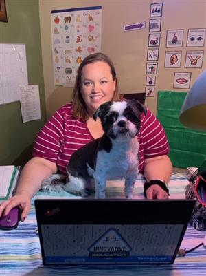 teacher online with a dog on her desk