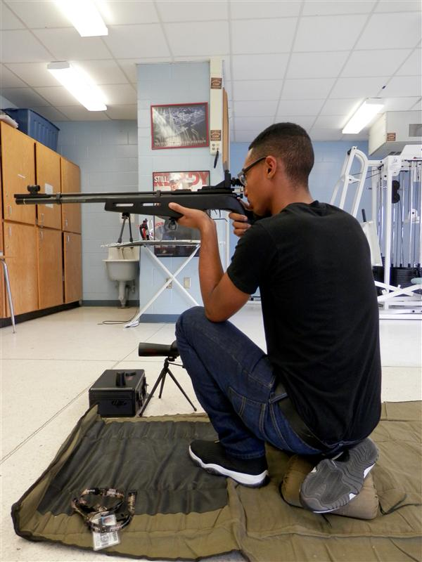 A cadet demonstrates the proper kneeling position with the rifle